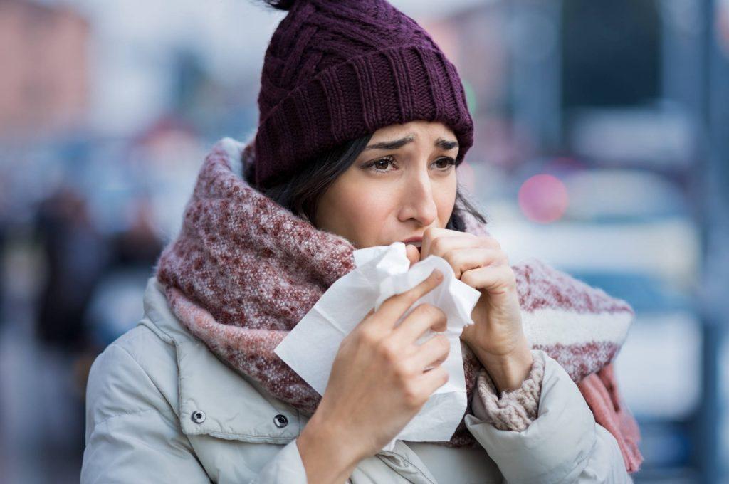 Kobieta w zimowym ubraniu kaszle w chusteczkę