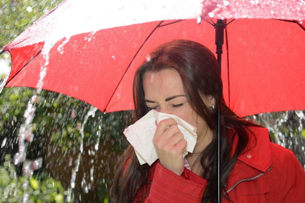 Kobieta pod parasolką kaszle w chusteczkę