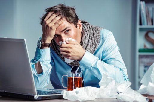 Chory mężczyzna siedzi przed komputerem, z kubkiem herbaty i dużą ilością chusteczek